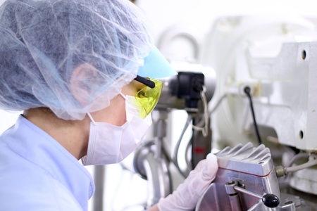 Pharmaceutical technician works in sterile working conditions at pharmaceutical factory.