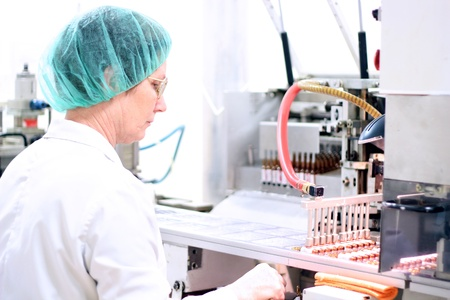 Robotic arm lifting ampoules at packaging line in pharmaceutical factory.