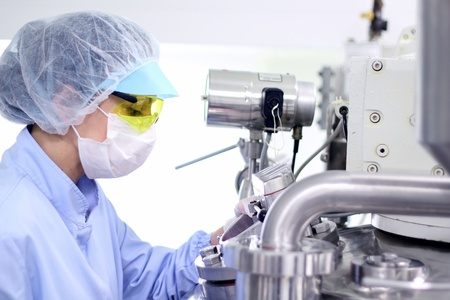 quality control: Pharmaceutical technician works in sterile working conditions at pharmaceutical factory.
