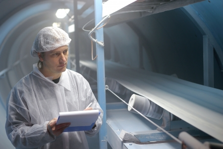 Quality inspector monitoring the process of crystal sugar production, Stockfoto