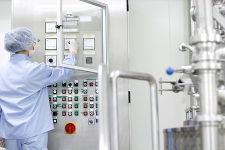 Female worker at pharmaceutical factory operating control panel of the pharmaceutical machine for medicine pill manufacturing  Selective focus