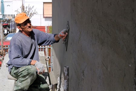 Mature contractor plasterer working outdoors  photo