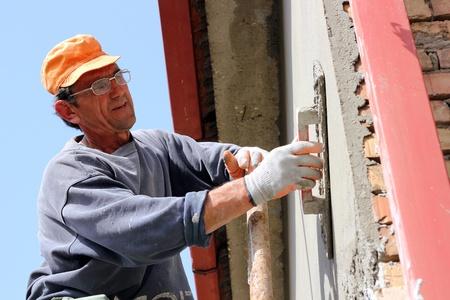 Mature contractor plasterer working outdoors