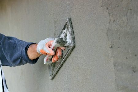 Man s hand plastering a wall with trowel  Selective focus  photo