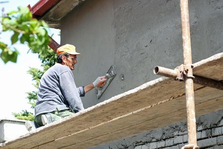 Mature contractor plasterer working outdoors   Selective focus  Standard-Bild