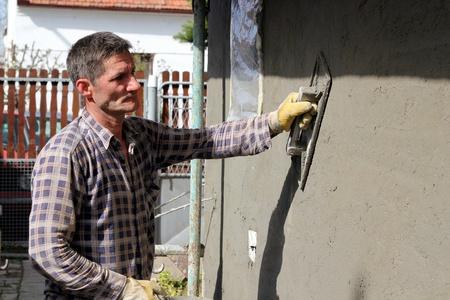 Mason worker plastering wall  photo