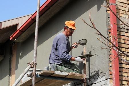 Mature contractor plasterer working outdoors  Selective focus