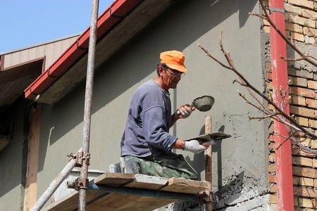 Mature contractor plasterer working outdoors  Selective focus  photo