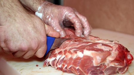 butcher's shop: Close-up of hands cutting raw meat   Selective focus  Stock Photo