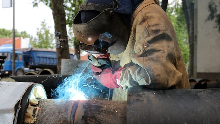 Welder with protective equipment welding outdoors  Selective focus  photo