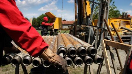 torres petroleras: Aceite de trabajadores de la plataforma de perforación de elevación del tubo de perforación Foscus está en el guante de protección y las tuberías Foto de archivo
