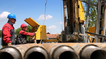 exploration: Oil drilling rig workers lifting drill pipe