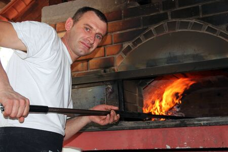 Pizza being baked in a wood fire brick oven in a restaurant   photo