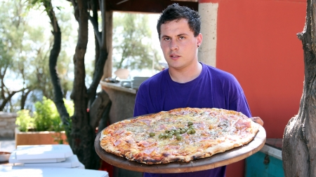 Portrait of a waiter with  large family pizza at an outdoor restaurant  photo