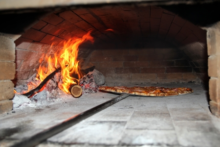 Pizza Baking in Wood Fired Oven  Inside view of the wood fired pizza oven   photo