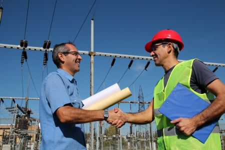 engineering clipboard: Engineer and Worker at Electrical Substation Stock Photo