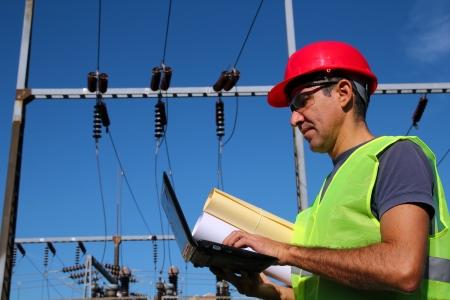ingenieria elÉctrica: Ingeniero Electricista con la computadora portátil y Planos Foto de archivo