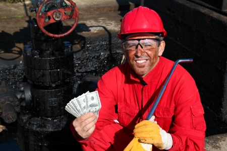 Happy Worker Holding Money at Oil Field  photo