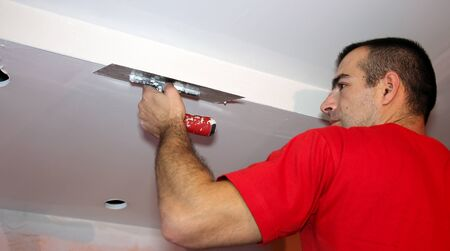 Man Applying Plaster on a Dry Wall photo