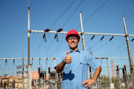 power distribution: Woker at an Electrical Substation Stock Photo
