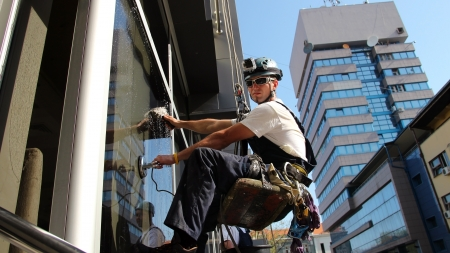 climber: Venster Wasmachines op een Office Building Stockfoto