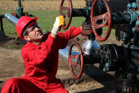 oil worker: Trabajador petrolero girando la v�lvula en la plataforma petrolera