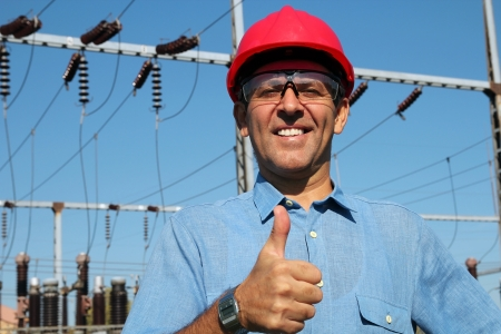 Thumb up given by smiling engineer next to electrical substation Stockfoto