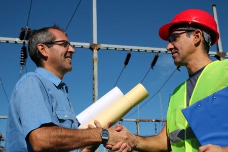 Power Company Workers on handshake Stockfoto