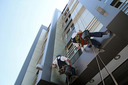 近代的なオフィスビルのファサードの窓洗濯の労働者 写真素材