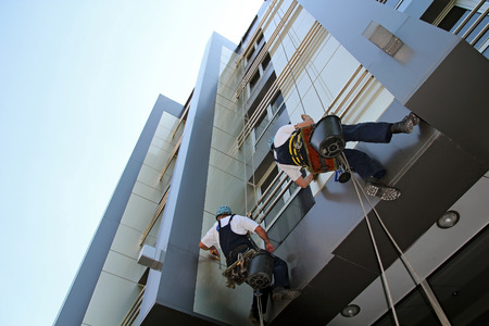 Trabajadores que lavan la ventana fachada de un edificio de oficinas moderno