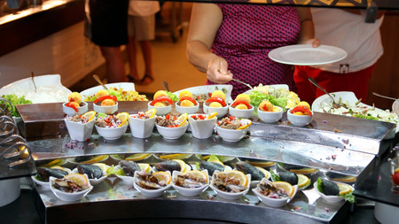 serv: Woman takes seafood from the buffet table Stock Photo