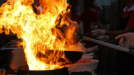 Chef Cooking With Fire In Frying Pan photo