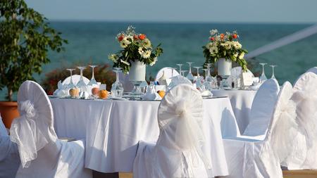 bodas de plata: Ajuste de la tabla al aire libre en la boda de recepción por el mar Foto de archivo