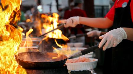 Chef-kok bakken voedsel in vlammende pan op gaskookplaat in commerciële keuken.