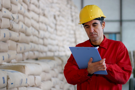 control de calidad: Trabajador Escribiendo en Clipborad en almac�n Foto de archivo
