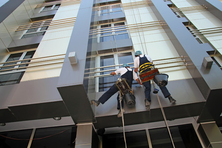 Industrial Climbers Washing Facade of a Modern Building