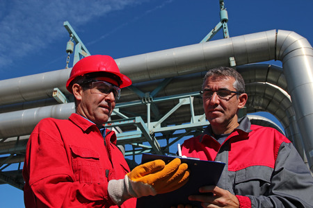 Engineer Signing a Document in Power Plant. Industrial workers with clipboard working in power plant. Stock Photo