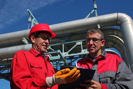 Inženýr Podepsání dokumentu v elektrárně. Průmyslové pracovníci s schránky pracují v elektrárně.