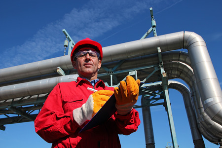 Oil Refinery Engineer and Pipelines. Worker wearing red overalls and hardhat , writing on clipboard next to pipelines. Stock Photo