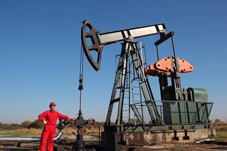 Oil Rig and Laborer. Worker in coveralls and safety goggles working on a drilling rig. photo