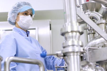 Pharmaceutical Manufacturing Technologist. Preparing machine for work in pharmaceutical factory.