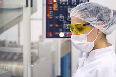 packaging industry: Woman Operating The Control Panel. Pharmaceutical Manufacturing Stock Photo