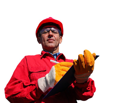 Worker wearing red overalls and hardhat , writing on clipboard next to pipelines, isolated on white.