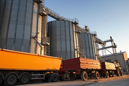 トラクターと穀物サイロの横にあるトラック