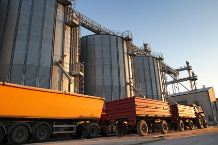 Tractor and Truck Beside Grain Silos