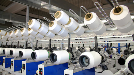 polyester: Row of automated machines for yarn manufacturing. Modern Textile Plant. Textile manufacturing of synthetic fibers.