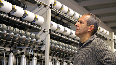 Engineer Examining Thread in Textile Mill