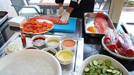 salmon ahumado: Pescados de color salmón ahumado Cocinero que rebana
