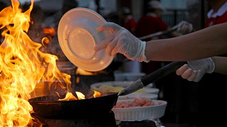 aceite de cocina: Cocinero en el trabajo - cocinar con llamas altas Foto de archivo