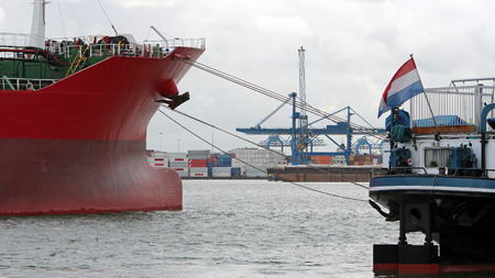 cargo vessel: Cranes and cargo containers alongside container ships moored at commercial dock. Industrial container freight trade port scene. Stock Photo